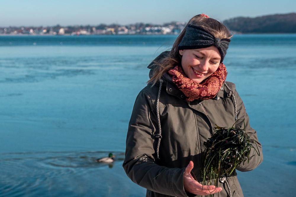 Frau hält Seegras in den Händen am Kieler Strand